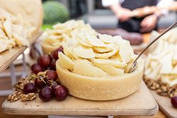 traditional-grana-padano-cheese-cutting-board-with-grapes-and-walnuts